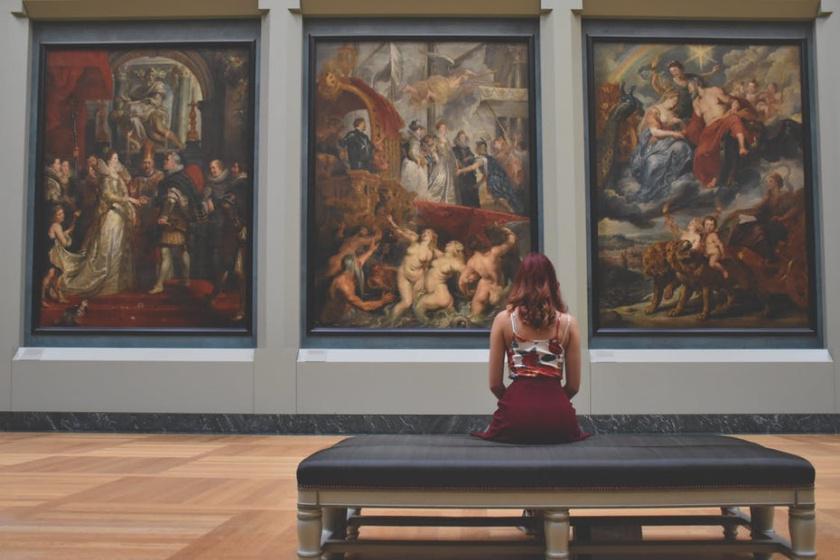 妇女坐在美术馆的绘画前